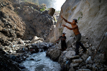 A man removes a rock as he searches for scrap metal at an area known as 'the Mine', in the largest garbage dump of Guatemala City