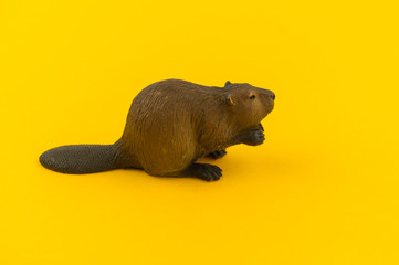Toy beaver from plastic on a yellow background.