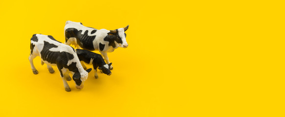 Toy cow made of plastic on a yellow background.