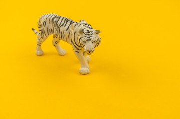 White albino tiger toy made of plastic on a yellow background.
