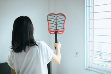 Asian woman using mosquito swatter at home,Female with mosquito electric net racket in bedroom