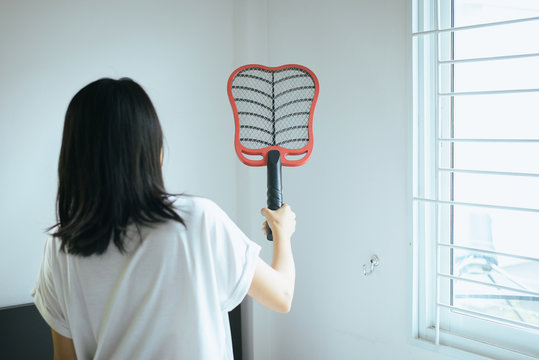 Asian woman using mosquito swatter,Female with mosquito electric net racket