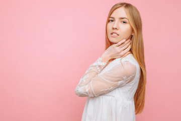 Portrait of a cute beautiful girl in white dress, on pink background