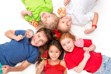 Close-up of happy children with candy lying on floor in studio and looking up, isolated on white background, top view. Kids emotions and fashion concept