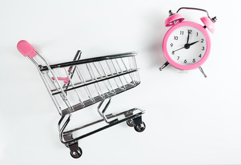 Female shopping time. Shopping cart and alarm clock pink color on a white background.