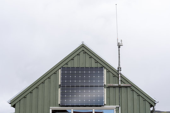 Cropped photo of little green house with small solar panel at the front of the building next to the cellular antenna against gray blue sky