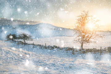 Beautiful Winter sunrise landscape over snow covered Peak District scene in heavy snow storm