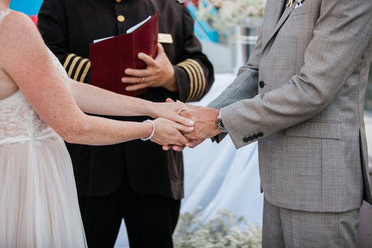 bride and groom holding hands during ceremony with officiant