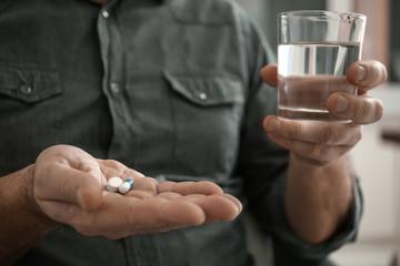 Mature man taking pills, closeup