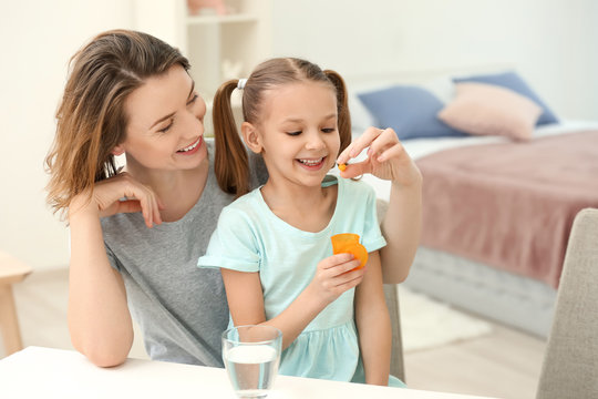 Young mother giving pill to her daughter at home