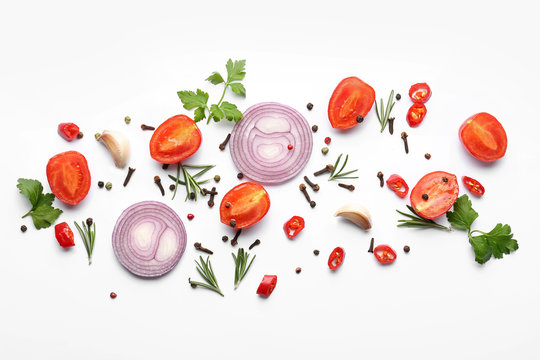 Cut vegetables, herbs and spices on white background, flat lay