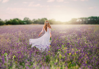 Photo sur Aluminium Lavende young lady dressed in an elegant long white dress with transparent sleeves and , with a neat hairstyle of blond hair decorated with a white wreath, walks across the field of purple flowers. no face