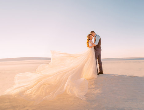Unusual wedding in the desert. A girl in a white dress ivory shade. Very long plume fluttering in the wind. A loving couple is embracing tenderly against the background of white sand and blue sky