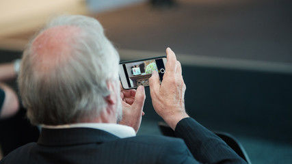 man with mobilephone makes pictures and is filming indoor