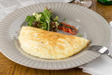 omelette and vegetables on grey plate on wooden table
