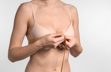 Young woman measuring her breast on light background