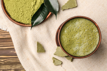 Cup of healthy matcha tea and plate with powder on table