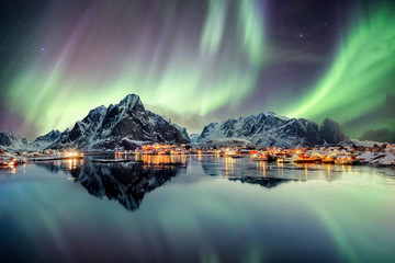 Aurora borealis dancing on mountain in fishing village