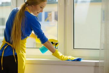 Woman cleaning windowsill