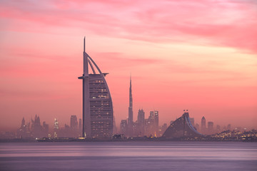 Stunning view of Dubai skyline from Jumeirah beach to Downtown lighted with warm pastel sunrise...