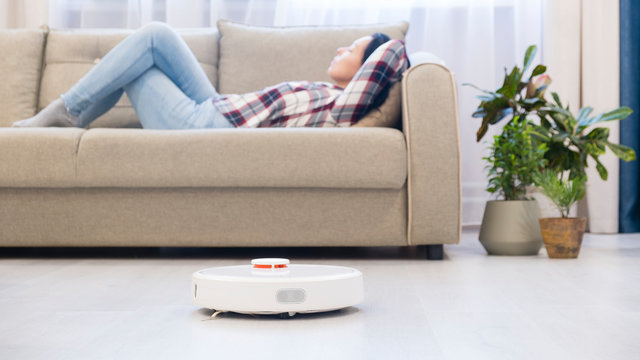 girl resting at home on the couch, while the robot vacuum cleaner. concept time for yourself. smart House. modern girl optimizes her time.