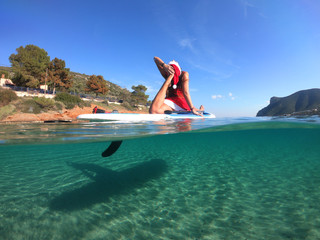 Underwater photo of attractive unidentified fit female dressed as Santa Claus practising SUP or Stand Up Paddle board at Christmas time