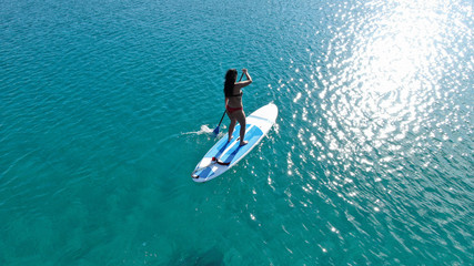 Aerial photo of fit woman practising SUP or Stand Up Paddle Board in tropical exotic sandy beach with emerald clear sea
