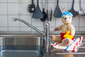 Indoor Bathing Season at Kitchen / Kitchen stainless steel sink as swimming pool - cute toy teddy bear in swimwear with rubber duck, bathing cap and towel wants to bath (copy space)