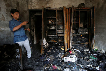 A man takes picture of a room in a residential building that was gutted by a fire on Thursday in Mumbai
