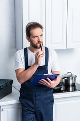 thoughtful bearded craftsman with clipboard standing in kitchen