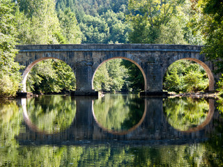.Symetrical reflection of an old road bridge in the River Cele near Sauliac sur Cele, Lot, Midi Pyrenees, France, Europe Wall mural