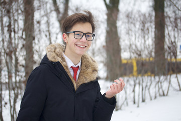 Portrait of a young man in a coat with a fur collar. Gestures while talking. On a walk in the winter park.