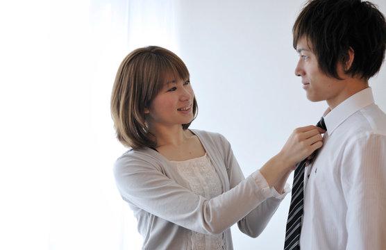 夫のネクタイを締める若い妻