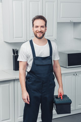 adult smiling bearded repairman in working overall holding toolbox in kitchen at home
