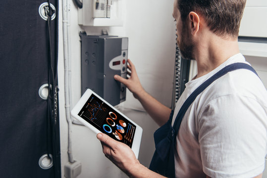 male electrician holding digital tablet with graphs on screen and checking electric box