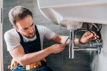 Fototapeta serious male plumber in working overall fixing sink in bathroom obraz