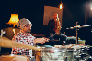Two men playing drums and saxophone in home studio.