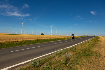 A motorcyclist in an agricultural landscape with wind turbines in the background