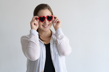 Smiling pretty woman adjusting heart shaped sun glasses. Lady wearing casual shirt and looking at camera. Valentines Day concept. Isolated front view on white background.