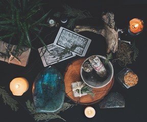 Dark flat lay of witchy items from nature including evergreens, burning candles, sage sticks, labradorite crystal and some tarot cards