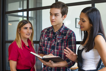 Portrait of three smiling students reading notes before lesson. Young Caucasian boy and two women standing and communicating at college. Education concept