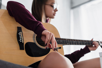 selective focus of girl sitting, holding marijuana joint and playing guitar at home
