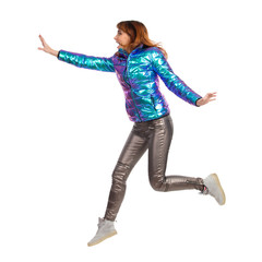 Young Woman In Shiny Pants And Vibrant Down Jacket Is Jumping. Side View.