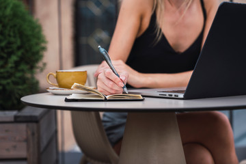 Young woman sitting on roof terrace taking notes, partial view