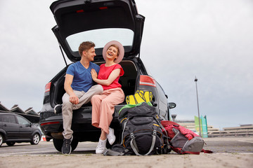 Happy young couple sitting in car boot at the airport