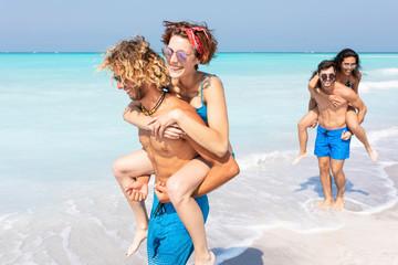 Friends walking on the beach, carrying girlfriends piggyback