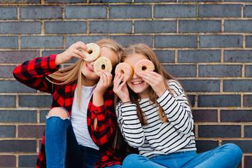 Two girls having fun with doughnuts