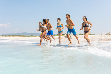 Group of friends having fun on the beach, running into the water