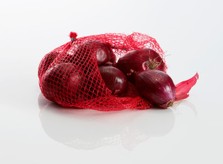 Net with red onions on white ground