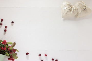 Festive white wooden background with two elegant vintage hearts and bouquet of fresh red berries with green leaves.